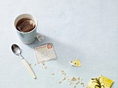 An arrangement featuring a tea cup, a note and scattered oats