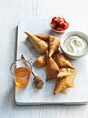 Deep-fried pastry parcels with lavender honey, strawberries and yogurt cream
