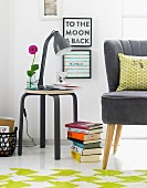 Schwarze Retro Tischleuchte auf farblich abgestimmtem Hocker montiert, daneben Bücherstapel auf Boden und teilweise sichtbarer Sessel mit schwarzem Lederbezug