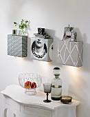 Selbstgebaute Wandleuchten, auch als Ablage, mit Tapete beklebt, weiße Wandkonsole mit Obstschale und rauchfarbener Glasflasche mit passendem Stielglas