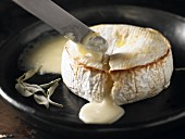 Baked Camembert cheese being cut