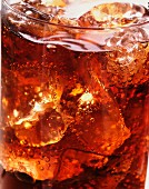 A glass of cola with ice and bubbles (close-up)