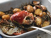Chicken breast stuffed with asparagus wrapped in Parma ham in a roasting tin with new potatoes, garlic and thyme