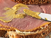 Mustard being spread on a ham sandwich (close-up)