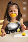 A little girl with Down Syndrome eating an orange