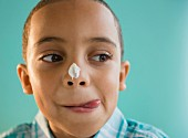 Junge mit Zuckerguss auf die Nase