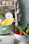 Fresh vegetables in a colander and spaghetti in a pot