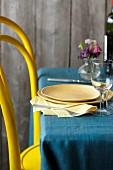 A yellow chair at a laid table