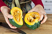 A woman holding two halves of acorn squash