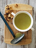 Asparagus and thyme soup with croutons and a rustic ladle