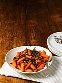 Baby carrots with sage butter and roasted walnuts on a wooden table