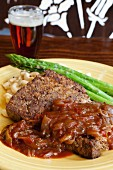 Meatloaf with macaroni and cheese served with asparagus and beer