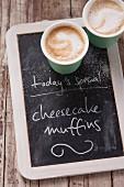 Zwei Coffee To Go auf Angebotstafel eines Coffeshops