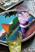 Farbige Trinkgläser mit Wasser und Eiswürfeln auf Tablett, darauf Abbildung vom Zuckerhut, Rio de Janeiro