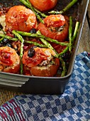 Oven-roasted stuffed tomatoes with olives and asparagus