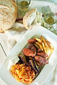 Sliced Greek sausage with roast potatoes, aubergines, feta cheese and tomato scrambled eggs