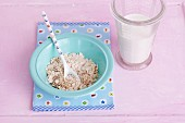 A plate of cereal grains a milk with a measuring jug