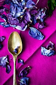 Dried hibiscus petals and an old spoon on a purple fabric napkin