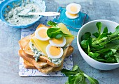 An egg sandwich with herb mayonnaise, cheese and lamb's lettuce