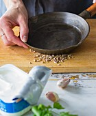 Coriander seeds being crushed with a pan