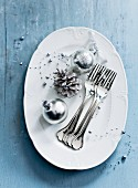 Silver Christmas baubles and forks on serving dish