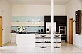 Freistehende Theke mit Ablagen und Designer Barhockern auf weißem Fliesenboden in offener, moderner Einbauküche