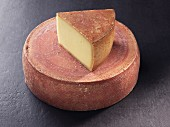 A wheel and a slice of Appenzeller cheese