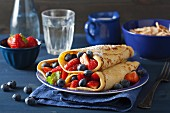 Pancakes with berries and icing sugar