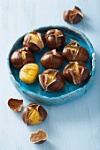 Roasted chestnuts in a blue ceramic bowl