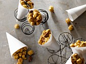 Caramel popcorn with almonds in paper cones