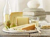 Slices of cheese with pears, crackers and white wine
