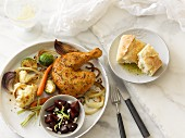 Chicken leg with herbs, cauliflower, carrots, brussels sprouts and onions served with a beetroot salad with goat's cheese and baguette