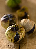 Five tomatillos in their husks on a wooden surface