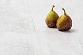 Two fresh figs on a white wooden surface