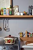 Retro Kochtopf auf Gasherd, darüber schmales Regalbrett mit Gewürzen