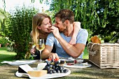 A man feeding his girlfriend at a picnic table in a garden