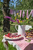 Tartlets and waffles with fresh cherries and a bunch of wild flowers in a jug on a garden table with a checked table cloth