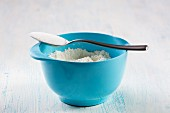 Baking ingredients: flour in a mixing bowl and a non-heaped spoonful of sugar