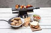 A raclette machine with ingredients in front of it
