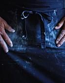 Mann wischt sich mehlverschmutzte Hände an Schürze ab