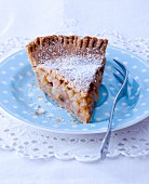 A slice of apple pie with icing sugar on a spotted plate
