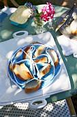 Brotkörbchen mit Fächern für Baguettescheiben und Servierplatte auf Frühstückstisch im Garten