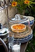 Aprikosentarte auf Korbteller mit Glashaube, Kaffeekanne und französisches Landhausgeschirr auf Eisenregal