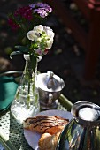 A breakfast tray in a garden with phlox flowers in a glass vase, croissants, a Thermos flask and a bowl of sugar