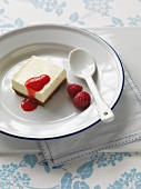 A panna cotta slice with raspberries and fruit sauce