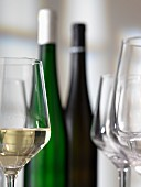 A glass of white wine, bottle of wine and empty glasses