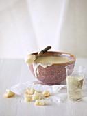 Kleines Käsefondue in einer Schüssel mit Brotwürfeln und Weißwein