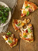 Slices of pizza with red and yellow pear tomatoes, basil and rocket