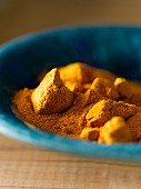 Turmeric powder and chunks in a blue bowl (close-up)