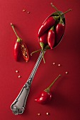 Red chilli peppers on a red surface